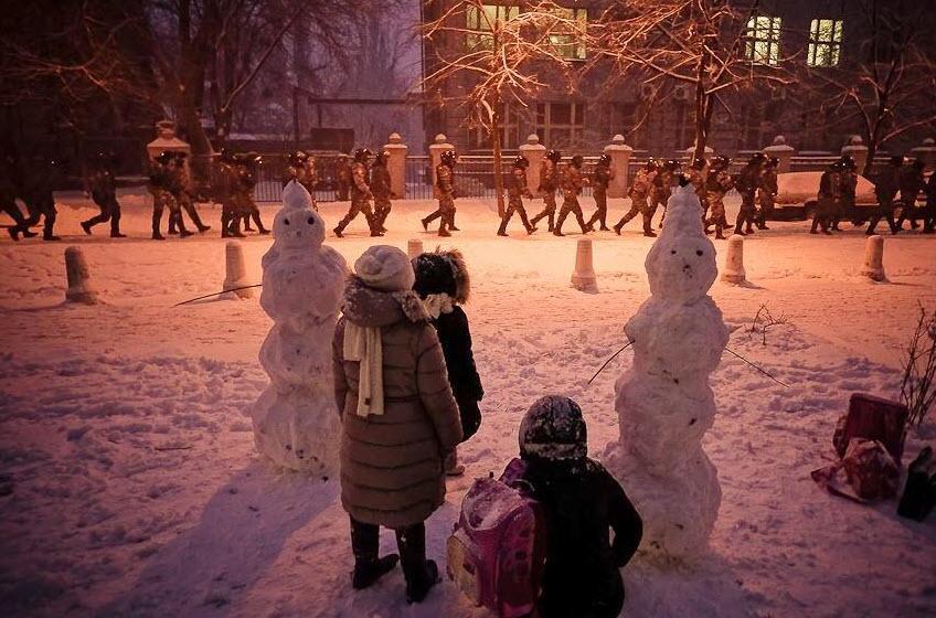 Unos niños ven desfilar a la Berkut o policía antidisturbios en las calles de Kiev