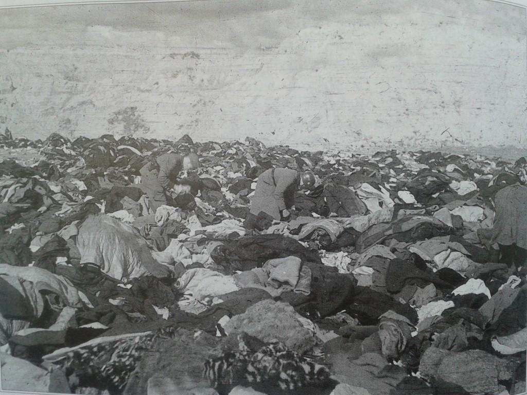 Soldados alemanes inspeccionan entre los restos de ropa de las víctimas