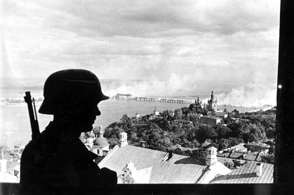Un soldado alemán en primer plano, mientras Kiev arde en llamas tras las explosiones de las minas